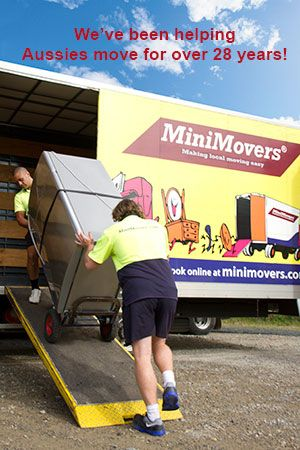 2 removalists moving a fridge inside MiniMovers truck