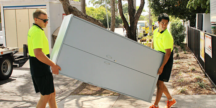 MiniMovers Professional Removalists carrying a heavy cabinet