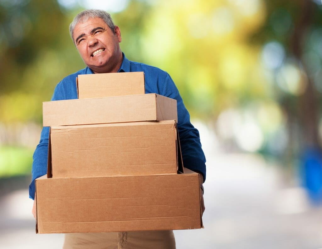 man having a hard time holding heavy boxes