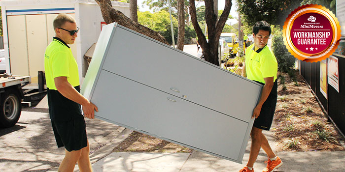 Professional removalists of MiniMovers lifting a cabinet