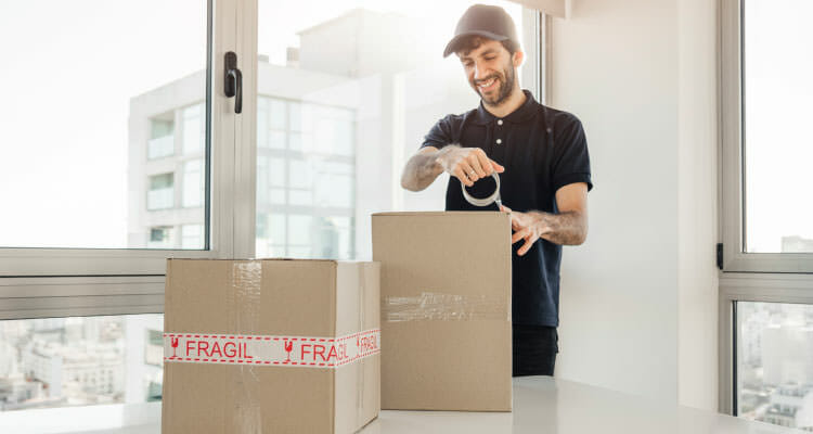 Guy packing fragile boxes