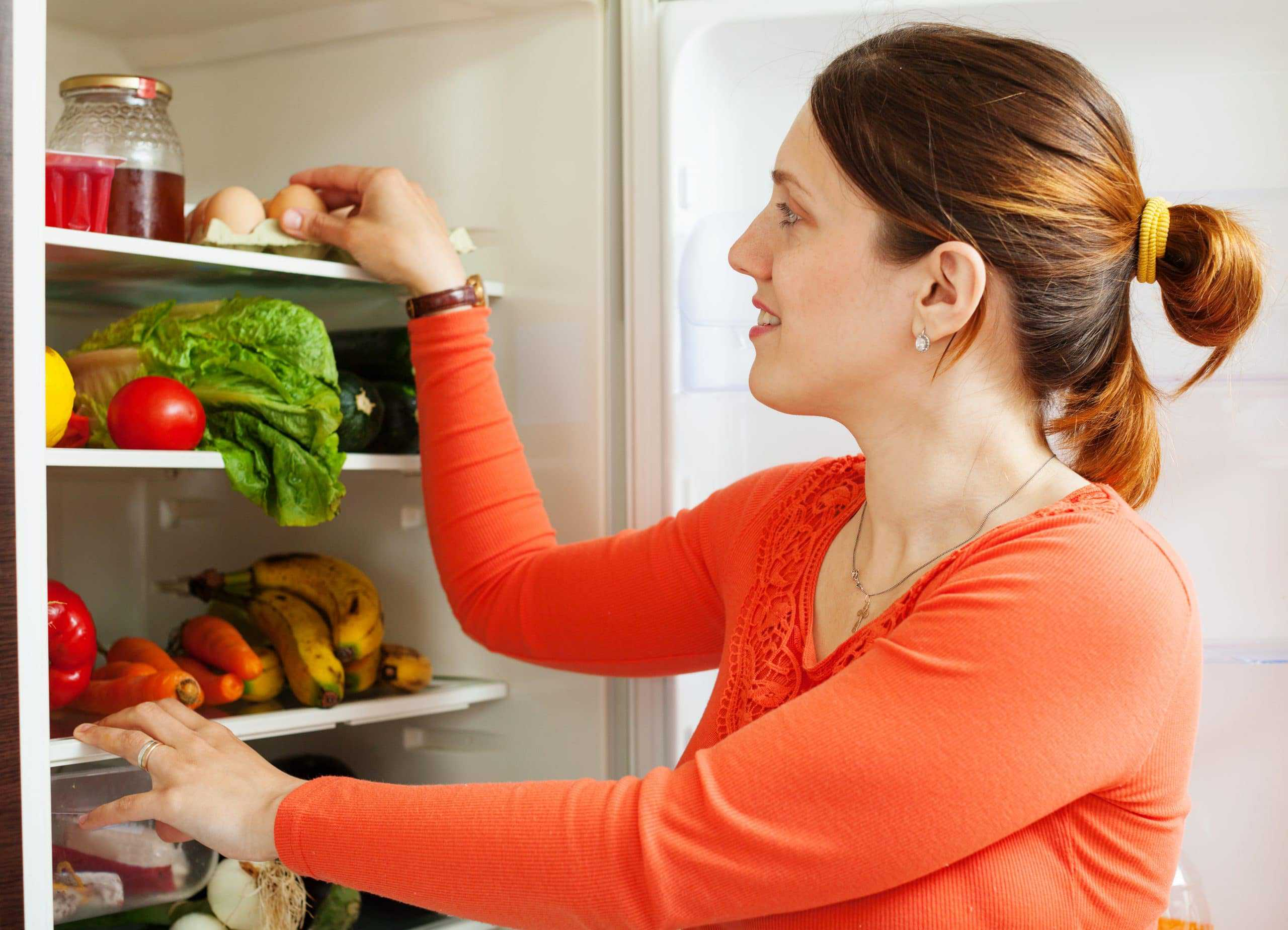 Woman organising fridge