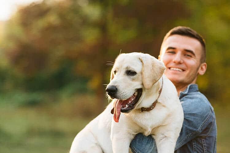 Guy holding a Labrador